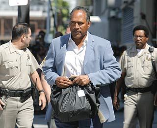 "<div class=""meta image-caption""><div class=""origin-logo origin-image ""><span></span></div><span class=""caption-text"">O.J. Simpson, center, leaves the Clark County Detention Center after he was granted bail in Las Vegas, Wednesday, Sept. 19, 2007. Simpson was released from jail Wednesday after posting $125,000 bail in connection with the armed robbery of sports memorabilia collectors at a Las Vegas hotel. Simpson, wearing a light blue sport coat and dark blue pants, carried a black bag as he strolled to a gray sedan with his lawyer and drove away from the Clark County Detention Center.  (AP Photo/Jae C. Hong)</span></div>"