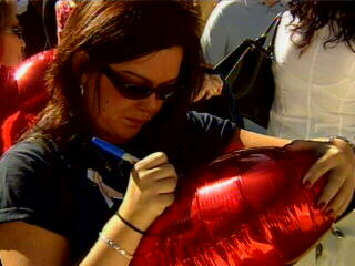 "<div class=""meta ""><span class=""caption-text "">A woman holds back emotion as she signs a ballon for a missed loved one. </span></div>"