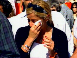 "<div class=""meta ""><span class=""caption-text "">A mourner wipes away tears as the victims' names are read. </span></div>"