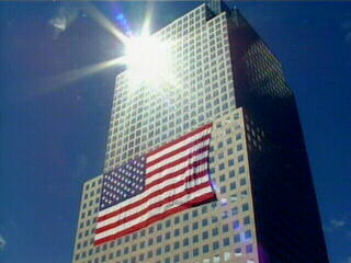 "<div class=""meta ""><span class=""caption-text "">Sunlight shines upon a nearby building draped with an American flag.</span></div>"
