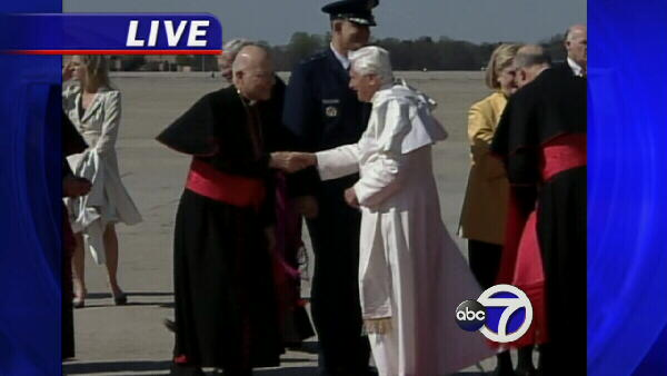 A religious official shakes hands with Pope Benedict XVI.
