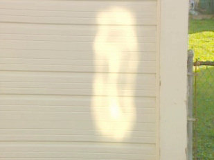 Every day in the early evening, dozens of people gather along Lewis Street in Minersville. Just as the sun begins to set behind a church just a few feet away, it appears. A reflected image on a garage that some here say is the image of the Virgin Mary
