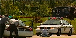9/2/2003: Forty-six-year-old Brian Douglas Wells sits on the street Thursday after the bank robbery, talking with Pennsylvania State Troopers in Erie.